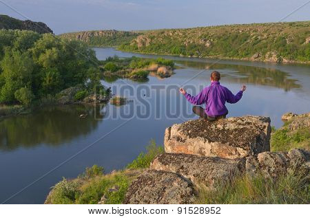 Spring landscape sunny day. A man sits on a stone and looking at the river
