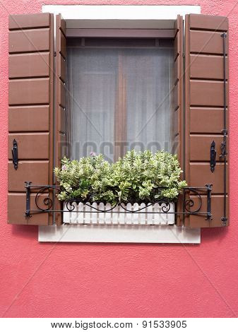 Burano, Italy - 21 May 2015: Red Painted Building. Close Up Of Window Shutters And Plant Box In Wind