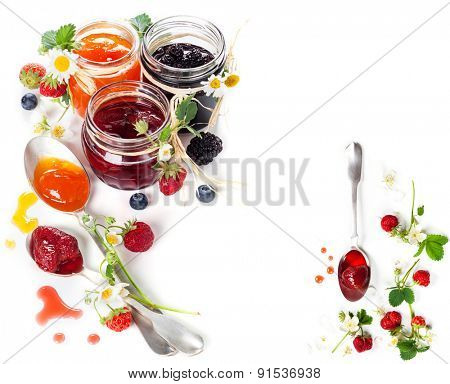 Different berry jam in jar and spoon