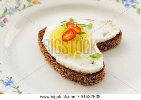 Fried Egg Heart Rye Sandwich With Scallion And Chili On White Plate
