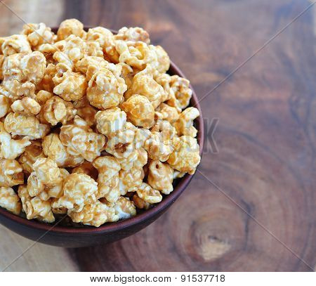 Golden Caramel Popcorn in a Bowl on a wooden table