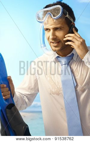 Workaholic young businessman on mobilephone on summer holiday, wearing shirt and tie and scuba diving equipments.