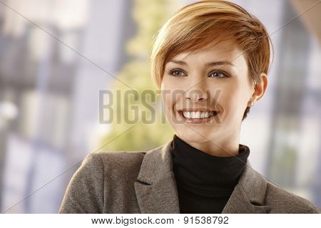 Closeup portrait of attractive young businesswoman in spring sunshine, smiling