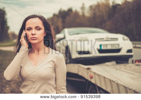Woman calling while tow truck picking up her car