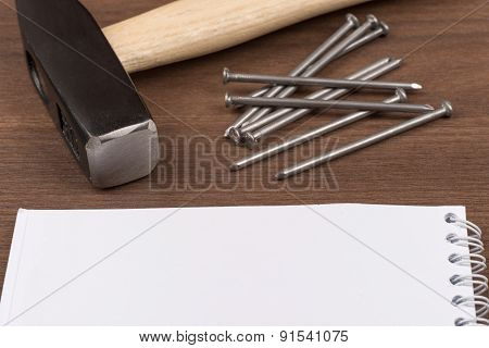 Hammer with note pad and nails on table