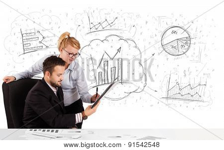 Business man and woman sitting at white table with hand drawn graph charts