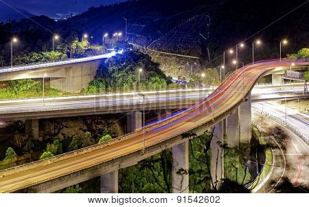 moving car on highway bridge with light through city at night