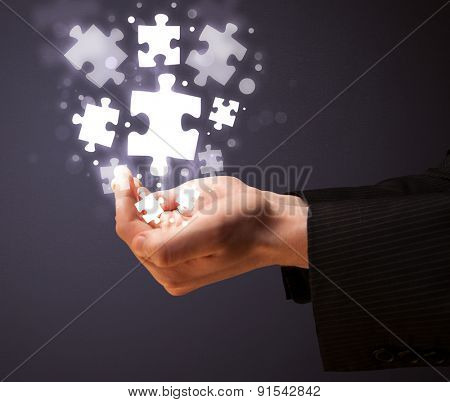 Businessman holding shining puzzle pieces in his hand