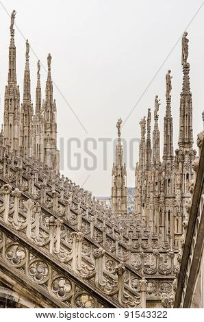 Vertical View Of Stone Sculptures On Roofs Of Duomo Milano
