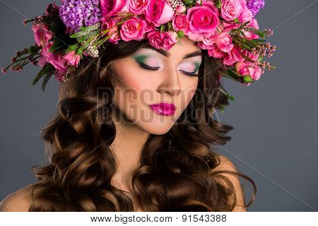 Studio Portrait Of A Beautiful Woman With Flowers Rose In Her Hair.