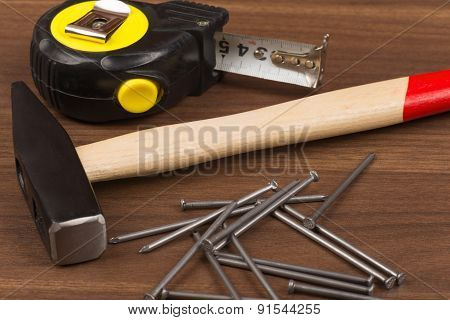 Hammer with steel tape and nails on table