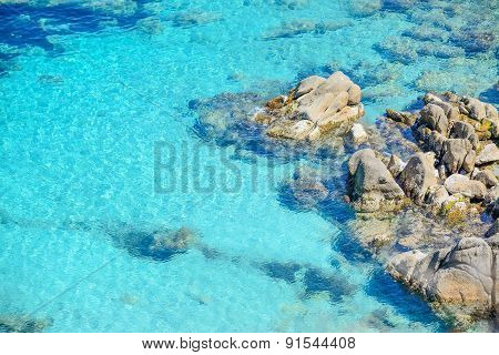 Grey Rocks In Capo Testa Clear Water