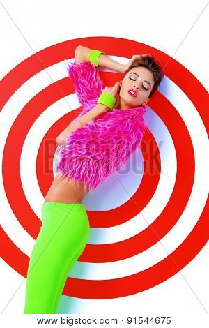 Fashion shot of a stunning female model posing in vivid colourful clothes over red target. Bright fashion. Studio shot.