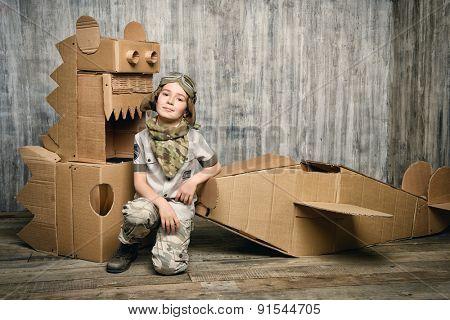 Cute dreamer boy playing with a cardboard airplane and dinosaur. Childhood. Fantasy, imagination.