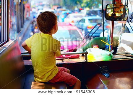 Young Boy Sitting In Local Public Bus, While Traveling Through The City Of Bangkok