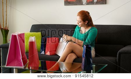 Latina Girl Peeps Into Shopping Bags On Sofa At Home