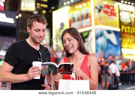 People in New York - happy couple on Times Square. Shopping young couple reading guidebook drinking coffee. Beautiful young couple having fun in city, Manhattan, USA. Asian woman, Caucasian man.