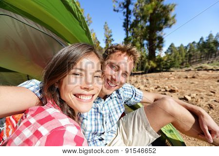 Selfie camping couple in tent taking self portrait using camera smartphone. Campers taking picture smiling happy outdoors in forest. Happy people having fun. Asian woman, Caucasian man.