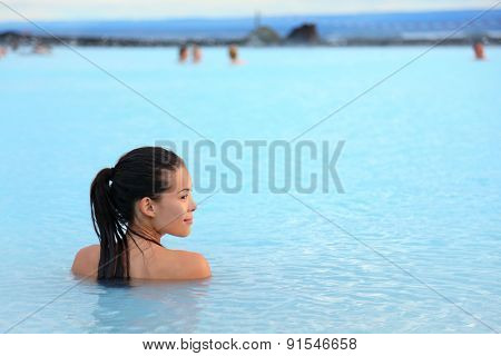 Geothermal spa. Woman relaxing in hot spring pool on Iceland. Girl enjoying bathing in a blue water lagoon Icelandic tourist attraction.