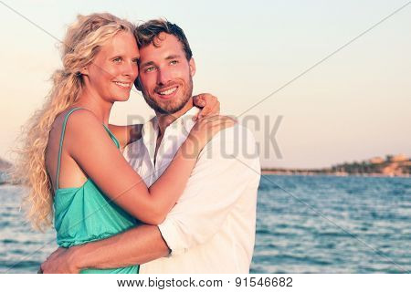 Romantic couple in love enjoying sunset at beach. Young happy woman and man lovers embracing and hugging in romance on summer beach during honeymoon vacation holidays travel.