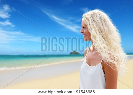 Blonde woman with long curly natural blond hair on beach in tropical paradise. Female model in her 20s smiling happy in profile.
