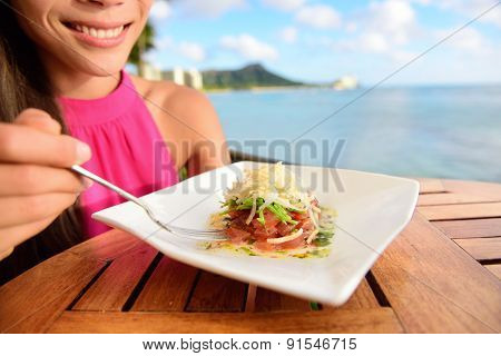 Tuna tartare. Raw ahi, Hawaiian food. Woman eating dish on Waikiki, Oahu, Hawaii.