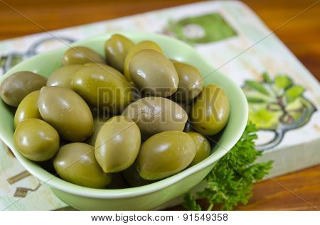Green Olives And Raw Parsley On A Decoupage Decorated Board