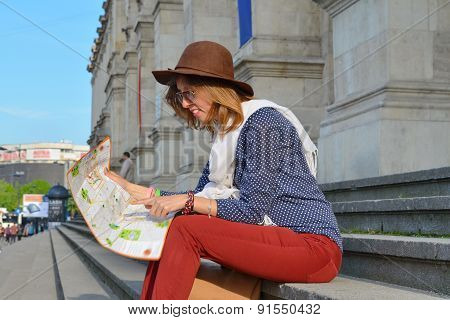 Young Girl Reading A Map Sitting On A Staircase