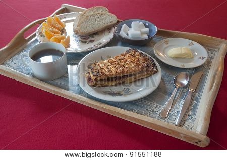 Breakfast set on a decorated tray with cake, coffee, bread, butter and orange wedges