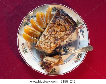 Piece of handmade cake with almonds and orange wedges on a decorated plate