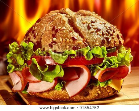 Hamburger with ham on wooden board on background of fire.