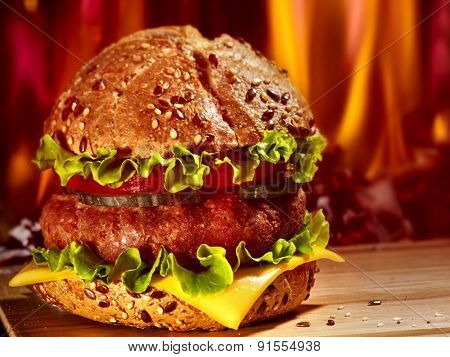 Double patty hamburger on wooden board on background of fire.