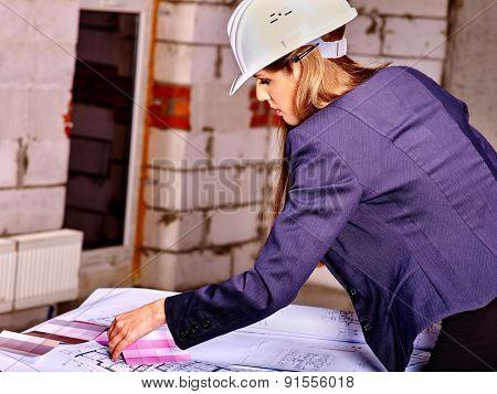 Business woman in builder helmet working indoor.