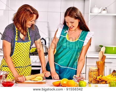 Mother and daughter cooking and talking food at kitchen.