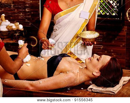 Woman having stomach ayurvedic massage with pouch of rice.