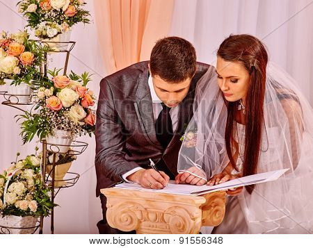 Groom and bride register marriage. Man puts his signature on wedding.