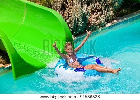Child on green water slide thumb up at aquapark. Summer holiday.