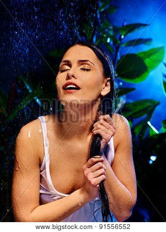 Wet woman with eyes closed under water drop. Nature.
