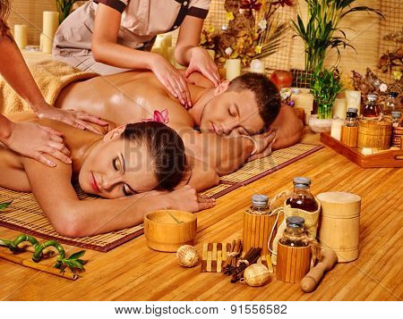 Man and woman relaxing in bamboo spa getting massage.