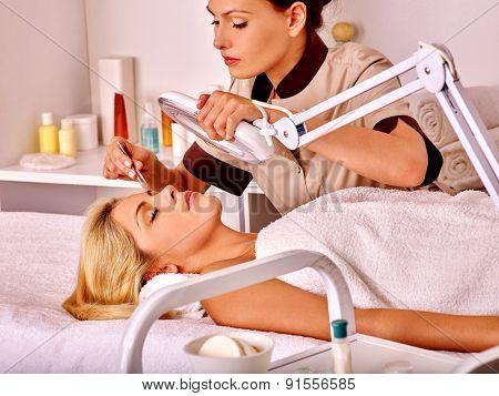 Woman getting tweezing eyebrow in beauty salon.