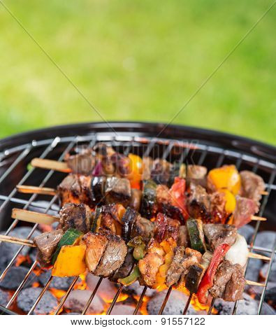 Delicious skewers on garden grill, barbecue time.