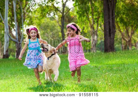 Two young girls running with a golden retriever on the grass in park