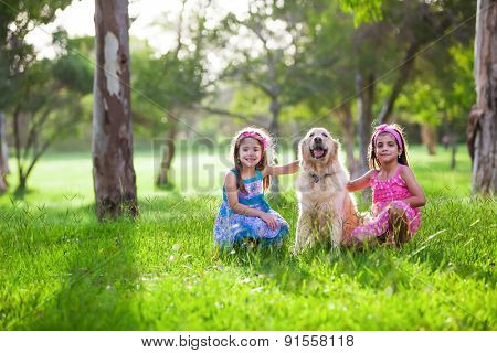 Two Beautiful little girls and their dog friend golden retriever in the park
