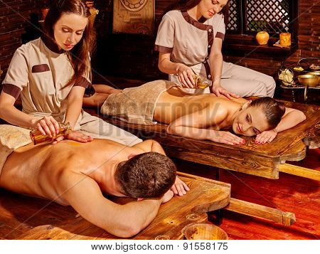 Couple  having oil Ayurveda spa treatment on exotic wooden bed.