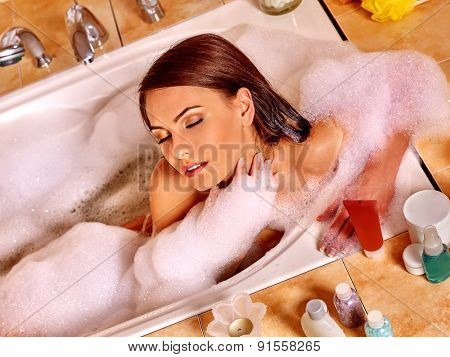 Beautiful woman with long hair relaxing at water in bubble bath.