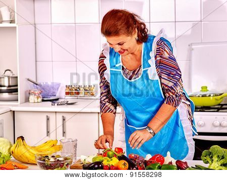 Mature woman in blue apron preparing dinner at kitchen.