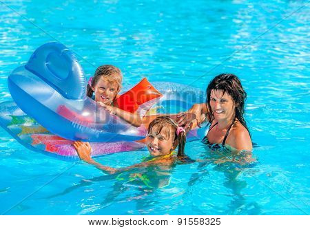 Family with children in swimming pool. Three people on summer outdoor.