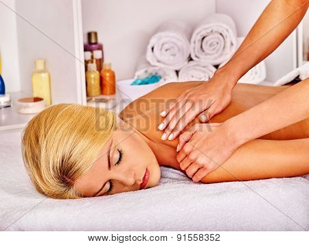 Blond sleeping woman getting massage in health resort.