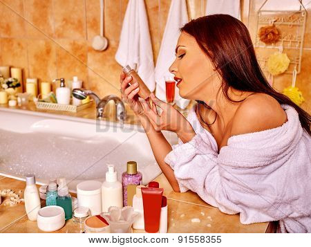 Woman in bathrobe applying moisturizer at bathroom.