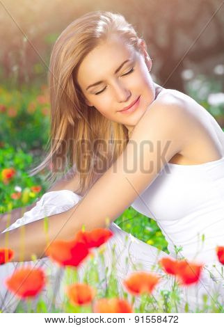 Calm blond female sitting on poppy flower field, woman with closed eyes enjoying enjoying beauty of nature, relaxation in countryside